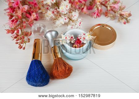 There White and Pink  Branches of Chestnut Tree,Two Make Up Brown and  Blue Brushes,Bottle Cream are on White Table,Top View