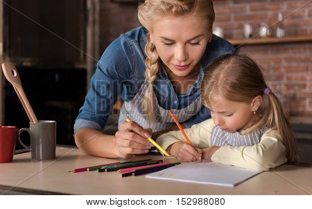 Happy free time. Delighted cheerful happy woman drawing with her daughter while sitting at the table and expressing joy in the kitchen