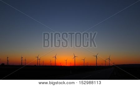 Burning sunset and wind mills silhouettes landscape