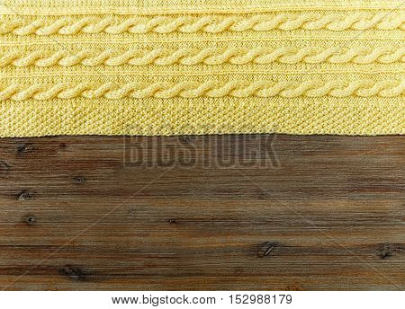 Knited yellow fabric with braid pattern on the wooden background.