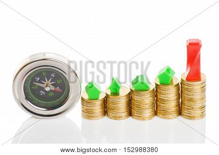 Stacks of coins, green and red home with compass. Mortgage concept by money house from coins