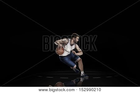 Professional basketball player in action isolated on black background