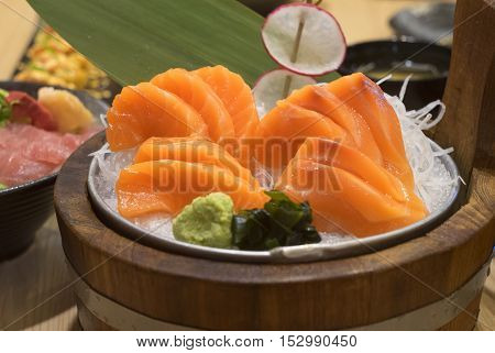 Salmon raw sashimi decorate on ice and wooden basket plate in japanese restaurant style.selective focus