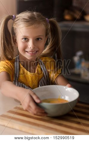 Look what I have done. Delighted cheerful little girl holding the bowl with broken eggs and standing near the table in the kitchen while expressing joy