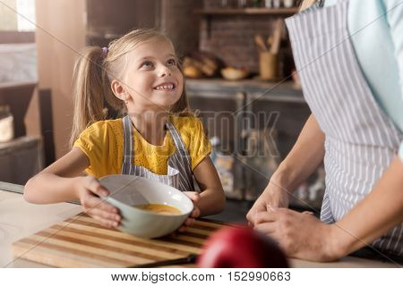 Full of delight. Pleasant beautiful smiling daughter holding and showing the bowl with broken eggs to her mother and standing near the table in the kitchen while cooking and having fun
