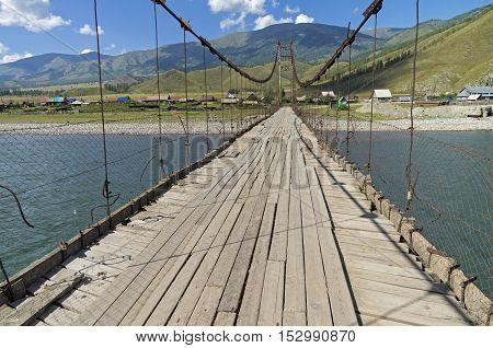 Old suspension bridge over the river Katun in the village Tungur. Altai Russia. Sunny summer day.