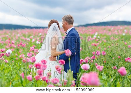Happy wedding couple in pink poppy field. Beautiful bride in white dress and groom kissing and having fun in flower field on summer day. Just married, young family.