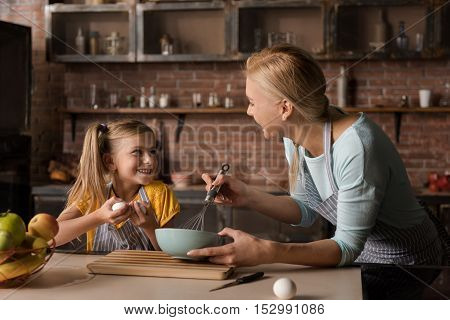 Full of delight. Delighted cheerful smiling girl holding eggs and standing near the table in the kitchen while her mother mixing eggs in the bowl