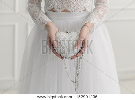 Handbag in form a heart in a hand of lady in white.
