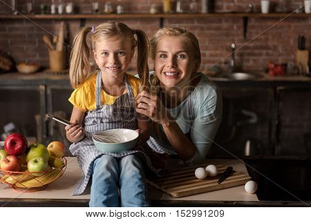 We like cooking. Cheerful merry smiling girl holding the bowl and mixing eggs while sitting on the table in the kitchen and cooking with her mother