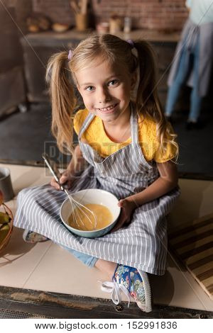 In a cheerful mood. Delighted amused smiling girl holding the bowl and mixing eggs while sitting on the table in the kitchen and her mother cooking in the background