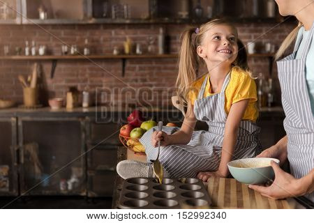 We enjoy baking together. Delighted amused smiling girl putting the pastry in baking rings while sitting on the table in the kitchen and cooking with her mother
