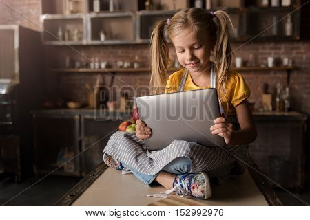 I searching for the bakery recipe. Pleasant delighted little girl holding and looking at the tablet while sitting on the table and expressing joy in the kitchen