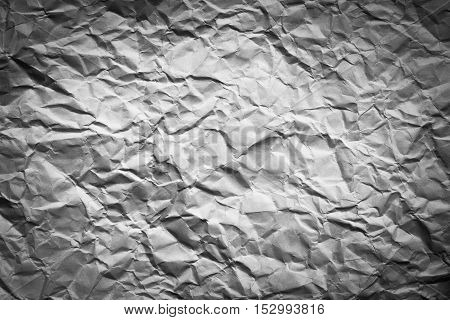 Texture of crumpled black and white paper with vignette.