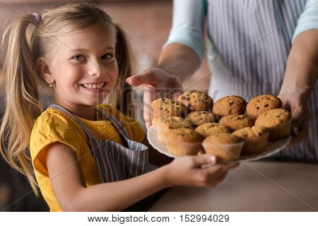 Look what we have baked. Pleasant amused little girl holding plate full of muffins with her mother while standing in the kitchen and expressing joy