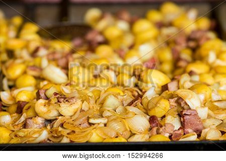 Baked potatoes for sale at the banquet on the street. Close-up of potato cooked with meat and onion