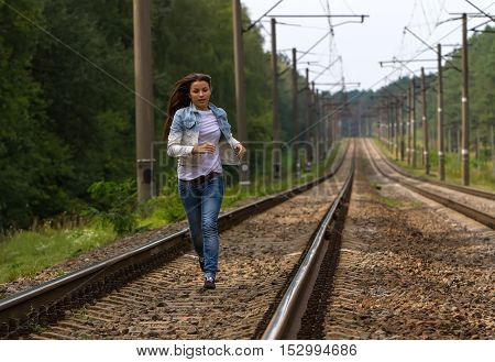 Girl with long dark hair, dressed in jeans running along the railway track.