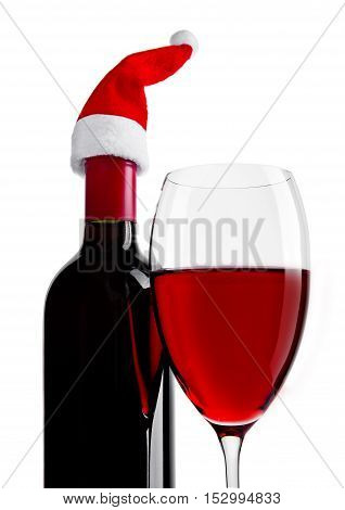 Bottle and glass of red wine with santa hat on white background