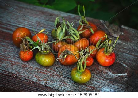 A pile of rose hips on a wooden board