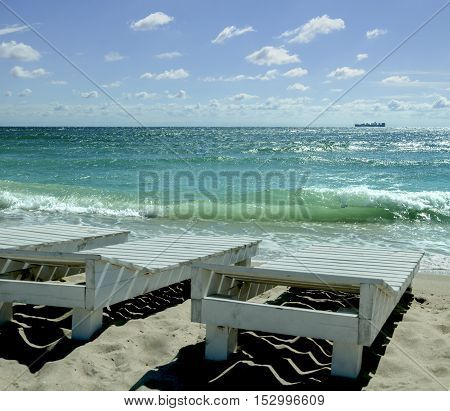summer warm day on the shore of the Black Sea with sun loungers on the sand