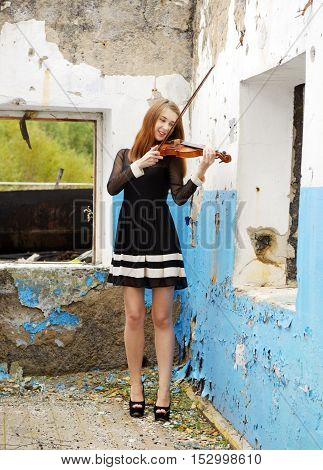 Beautiful woman with violin inside old broken house