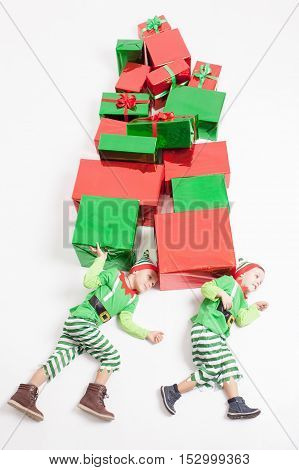 Funny two boys dressed in Elf costumes holding many gift boxes. Black Friday 2016. Celebrating Christmas. Copy space at white background. Big gift box. Cristmas shopping. Merry Christmas. Big Sales