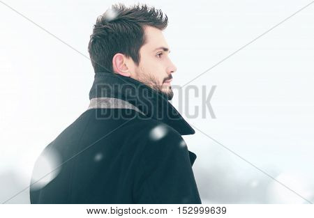 Portrait of fashion handsome elegant free man in winter snowstorm looks into distance view profile flying snowflakes
