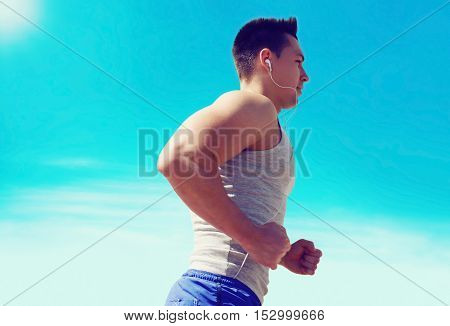 Sport fitness workout and healthy lifestyle concept - athlete man running listens to music in earphones over blue sky in sunny summer day view profile