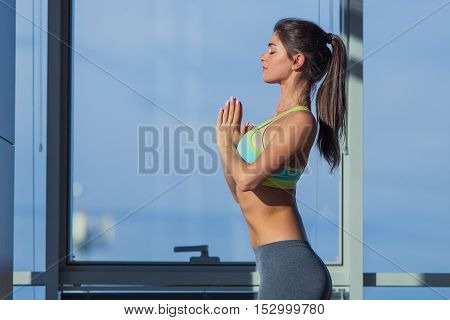 fitness, sport, training and lifestyle concept -  woman stretching on mat in gym. light from a large window