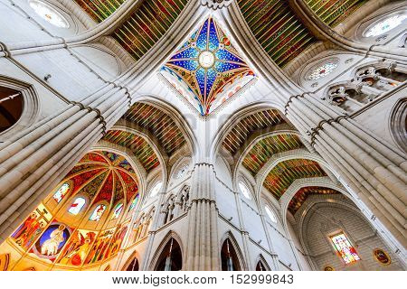 MADRID SPAIN - NOVEMBER 4 2015: Symmetrical view of beautifully lit Santa Maria la Real de La Almudena cathedral colourful decorated ceiling with windows from below.