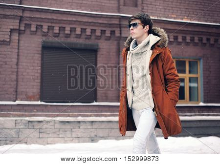 Fashion Man Wearing A Jacket Walking In City Over Brick Wall Background Looks Away View Profile