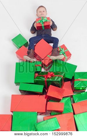 Merry Christmas 2016. Black friday. Happy boy holding Cristmas gift at the top of many gift boxes. Child happy to receive present. Shopping sale at Xmas. Cyber Monday US