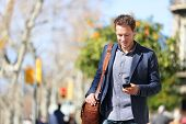 Young urban businessman professional on smartphone walking in street using mobile phone app texting  poster