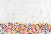 Sugar sprinkles on a white icing background.