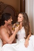 foto of lewd  - Young sexy heterosexual couple celebrating with wine in bed - JPG
