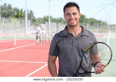 tennis player posing in front of a tennis court