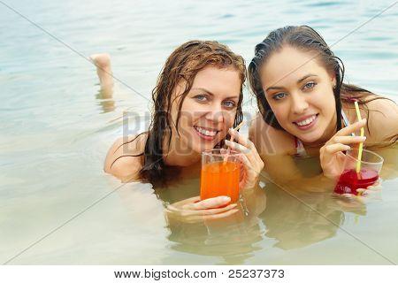 Retrato de dos niñas felices celebración de vasos con jugo fresco mientras se relaja en el agua