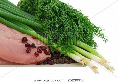 Raw Turkey Breast With Green Vegetables And Cranberries On Plate