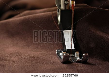 Sewing machine presser foot with threaded needle raised mid-seam on brown suede cloth.  Macro with extremely shallow dof and copy space.
