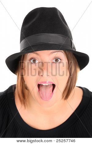 A portrait of a pretty young woman in a black hat sticking out tongue over white background