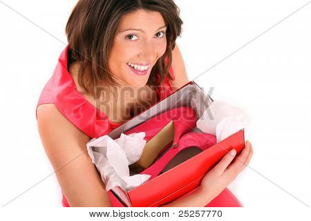 A picture of a happy woman holding her shoes over white background