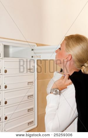 Woman is standing in front of her letter box and is looking after her mail