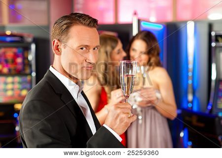 Three friends with champagne in a bar or casino, a man is looking in the camera