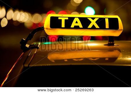 Taxi cab sign on top of the vehicle at nighttime