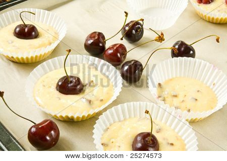 Unbaked muffins in paper muffin cases on a baking sheet decorated with cherries