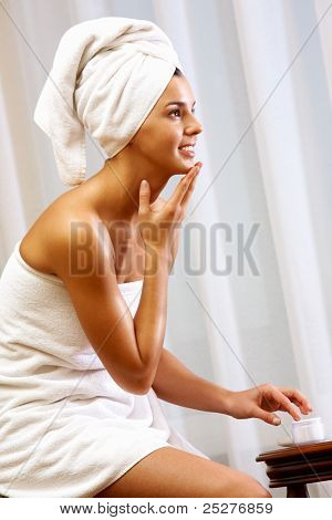 Portrait of pretty female applying cream onto her face after bath