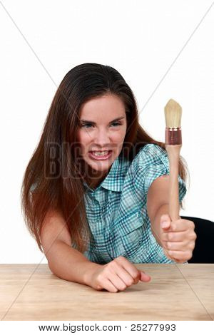 Brown-haired woman baring her teeth and holding a paintbrush