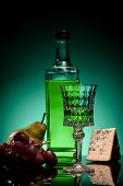 Close-up Shot Of Absinthe With Fruits And Cheese On Mirror Surface On Dark Blue Background poster