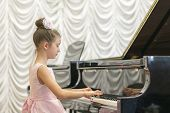 Girl In A Beautiful Pink Dress Playing On A Black Grand Piano. Girl Playing On A Black Piano. poster
