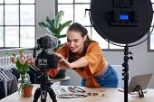 Young female vlogger adjusting her video equipment to record for her lifestyle fashion channel poster